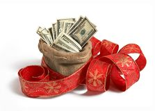 Bag of money. Studio photography of bag full of hundred dollar bills, decorated with red Christmas ribbon stock photo