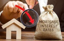 Bag with the money and the word Mortgage interest rates and arrow down and house. Low interest in mortgages. Reducing interest royalty free stock images