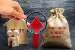 Bag with the money and the word Mortgage interest rates and up arrow with family and home. Raising mortgage rates and tax. The royalty free stock image