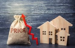Bag with the money and the word Price and up arrow and wooden houses. The increase in housing prices. Rising in fees for an. Apartment. The rise in property stock photo
