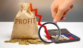 Bag with money and word profit and down arrow with calculator. Unsuccessful business and poverty. Profit decline. Loss of. Investment. Low wages. Economic royalty free stock photo