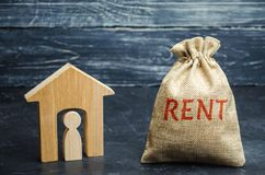 A bag with money and the word Rent and a house with a tenant inside. The accumulation of money to pay rental housing. Rental. Apartment. Saving money. Renting a royalty free stock photos