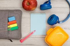 Bag-pencil case with color felt pens and marker, apple, notebook. Bag-pencil case with color felt pens and marker, apple, blue notebook, headphones and lunch box royalty free stock photos