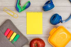 Bag-pencil case with color felt pens and marker, apple, notebook. Bag-pencil case with color felt pens and marker, apple, yellow notebook, stapler, headphones royalty free stock photo