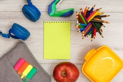 Bag-pencil case with color felt pens and marker, headphones, sta. Pler, yellow notebook, apple, color pencils and lunch box on grey wooden background. Top view royalty free stock image