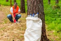 Bag of plastic bottles near tree Stock Photo