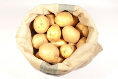 Bag with potatoes on white Stock Photography