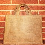 Bag for products from natural burlap with handles against a brick wall stock photos