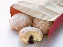 Bag Of Raspberry Jam Doughnuts With A Bite Taken Stock Photos