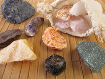 Bag with raw gemstones for water revitalization. On table Royalty Free Stock Images