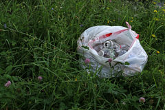 Bag of recyclables in grass. Recyclables in white trash bag found in grassy area beside a ditch Royalty Free Stock Images