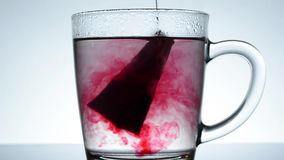 Bag of red tea is brewed in a glass mug close up full-HD stock video