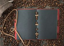 A bag of roasted arabica coffee beans and a dark paper note. On a black wooden background top view Royalty Free Stock Photography