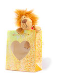 Bag's Lion. Little stuffed lion with small gift bag over white background Stock Photos