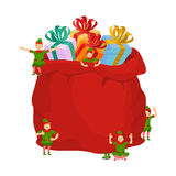 Bag Santa with gifts and Christmas elves. Red sack with toys and Royalty Free Stock Photos