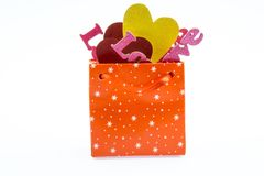 Bag scarlet for gifts with colorful hearts and decorative words. Bag with gifts in the form of colorful hearts and the words `love stock image