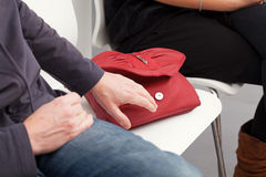 Bag stealing. The pickpocket is going to steal the woman's red bag Stock Image