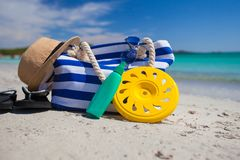 Bag, straw hat, sunblock and frisbee on white. Beach bag, straw hat, sunscreen and a frisbee on the white sandy tropical beach Royalty Free Stock Images