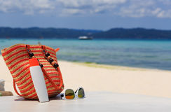 Bag, sun glasses and suncream on tropical beach Stock Photography