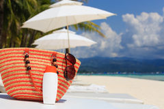 Bag, sun glasses and suncream on tropical beach Royalty Free Stock Photography