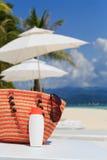 Bag, sun glasses and suncream on tropical beach Stock Image