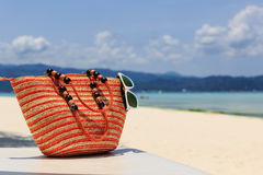 Bag and sun glasses on tropical beach Stock Photo