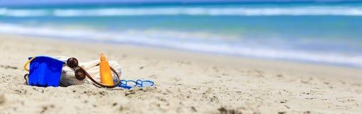 Bag, suncream, kids toys on the beach Stock Photos