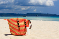 Bag and suncream on tropical beach Royalty Free Stock Photos