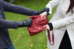 Bag theft. Thief is assaulting a girl to steal a handbag Royalty Free Stock Images