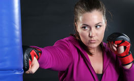 Bag Time. Pretty Young Brunette Woman Punching a Heavy Bag wearing Mixed Martial Arts Gloves royalty free stock photo