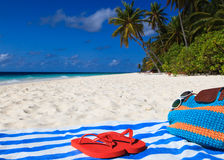 Bag, towel and flip flops on a tropical beach Royalty Free Stock Photography