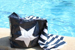 Bag and towel beside Swimming Pool. Swimming Pool with bag and towel in front of the picture Royalty Free Stock Photography