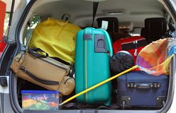 Bag and trolley with a fishing net in the trunk of the car. Duffle bag and trolley with a fishing net in the trunk of the car departing Stock Images