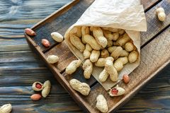 Paper bag with unshelled peanuts. Bag with unshelled peanuts on an old wooden box, selective focus Royalty Free Stock Image