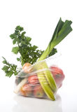 Bag with vegetables. Grocery-bag with vegetables and fruits isolated on a white background with a soft reflection Stock Photography
