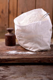 Bag of whole flour on wooden background Royalty Free Stock Photo