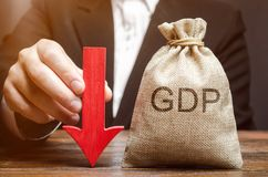 A bag with the word GDP and a down arrow in the hands of a businessman. Decline and decrease of GDP - failure and breakdown of. Economy and finances leading to royalty free stock photos