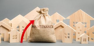 A bag with the word Maintenance, wooden houses and up arrow. Rising costs for the maintenance of housing, large bills. Expensive stock photo