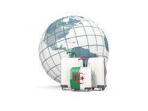 Bagaż z flaga Algeria Trzy torby przed kulą ziemską Zdjęcie Stock