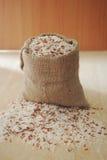 Baga do arroz, arroz integral em um pano no fundo de madeira, ainda li Fotos de Stock