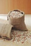Baga do arroz, arroz integral em um pano no fundo de madeira, ainda li Fotos de Stock Royalty Free