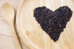 Baga do arroz do coração em umas bacias de madeira com a colher no fundo de madeira Fotografia de Stock