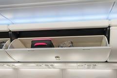 Bagage à main en compartiment aérien de stockage sur l'avion photos stock