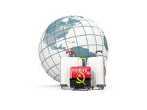 Bagage avec le drapeau de l'Angola Trois sacs devant le globe Image stock