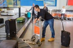 Bagage de attente d'homme de bande de conveyeur à l'aéroport Image libre de droits