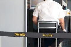 Bagage de balayage d'homme au point de contrôle de sécurité dans les aéroports Image stock