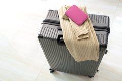 Bagage de déplacement dans le terminal d'aéroport avec le passeport et le chandail Image libre de droits