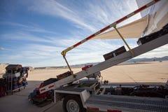 Bagage laddas i en passagerarenivå på en grov asfaltbeläggning Härlig dag på flygplatsen med dramatiska moln royaltyfri fotografi