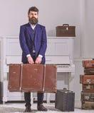 Bagage och resande begrepp Macho stilfullt på strikt framsida står och bär den stora tappningresväskan Man handelsresande fotografering för bildbyråer