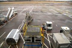 Bagagekar en Ander Behandelingsmateriaal op het Tarmac van een Luchthaven stock afbeeldingen